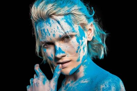 portrait of passionate girl in blue holi powder, isolated on black