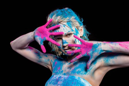 attractive girl gesturing and posing in pink and blue holi powder, isolated on black