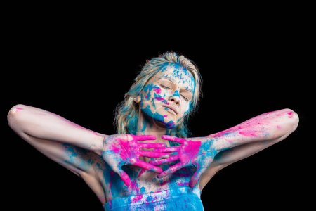 blonde girl posing with closed eyes in pink and blue holi powder, isolated on black