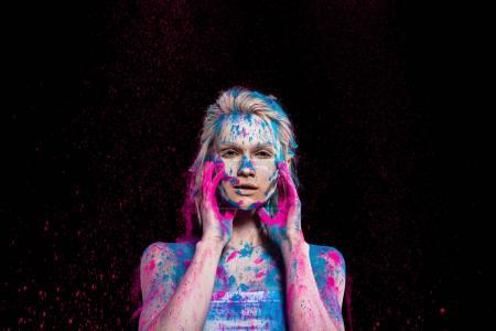 fashionable girl posing in pink and blue holi powder, isolated on black