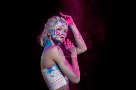 attractive young woman posing in pink and blue holi paint, isolated on black