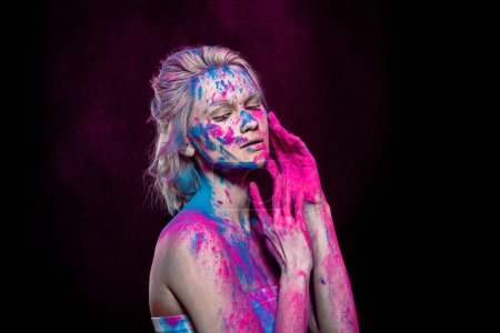 tender girl posing in pink and blue holi powder, isolated on black