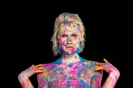 beautiful blonde girl posing in colorful holi powder, isolated on black