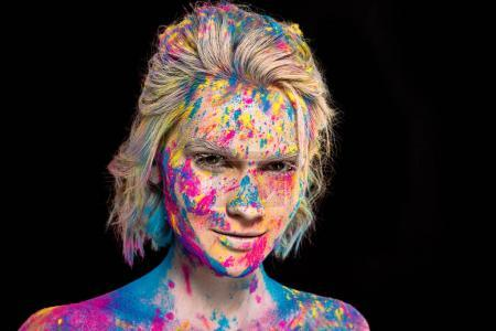 portrait of smiling girl in colorful holi paint, isolated on black