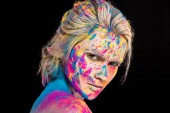 attractive fashionable girl posing in colorful holi powder, isolated on black