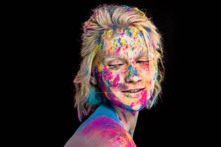 beautiful happy girl in colorful holi powder, isolated on black