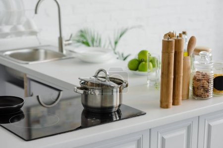Photo for Pan on electric stove, ripe delicious apples at kitchen counter - Royalty Free Image
