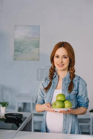 Photo for Beautiful pregnant woman holding plate with ripe apples at kitchen - Royalty Free Image