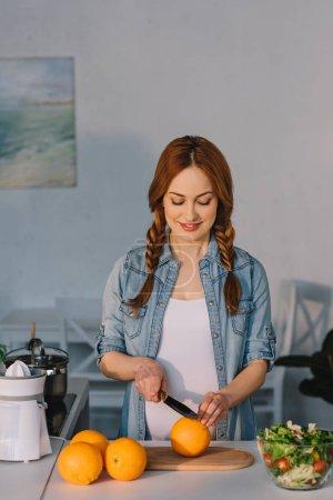 Photo pour Oranges coupe heureux jolie femme enceinte à la cuisine - image libre de droit