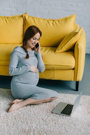 Photo pour Jolie femme enceinte assis sur le plancher et de parler de smartphone dans le salon - image libre de droit