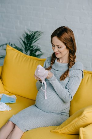 attractive pregnant woman looking at baby hat in living room