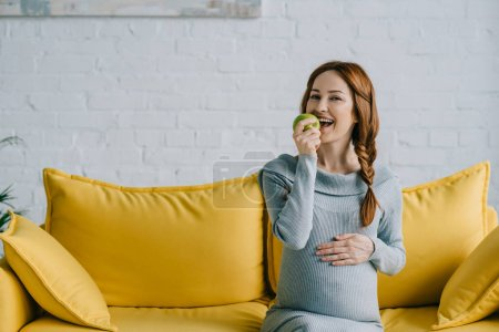 happy attractive pregnant woman eating apple in living room