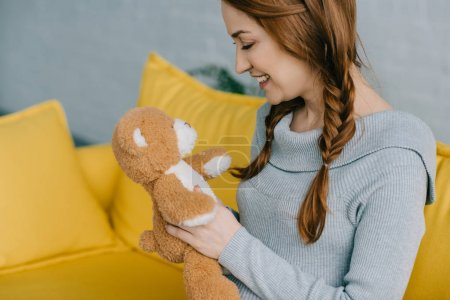 side view of beautiful pregnant woman looking at teddy bear in living room