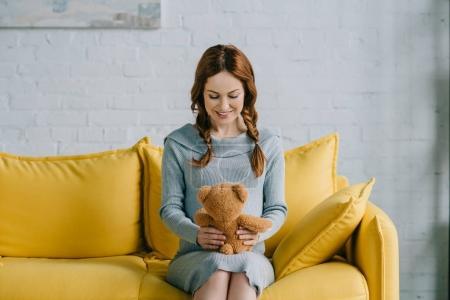 Photo pour Belle femme enceinte assise avec ours en peluche dans le salon - image libre de droit