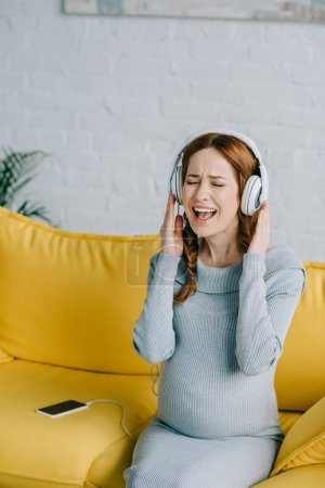 happy pregnant woman listening to music and singing in living room