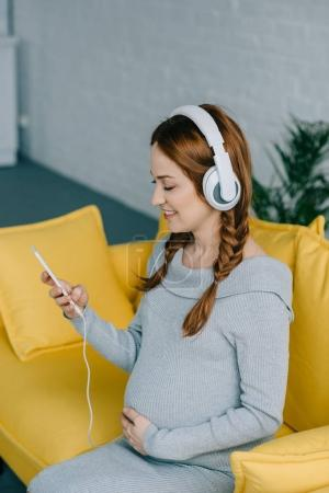 Photo pour Gaie femme enceinte écouter de la musique dans le salon - image libre de droit