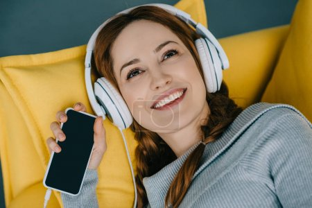 Photo for Happy woman lying on sofa and listening to music with smartphone - Royalty Free Image