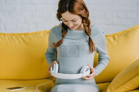 beautiful pregnant woman putting headphones with music on belly in living room
