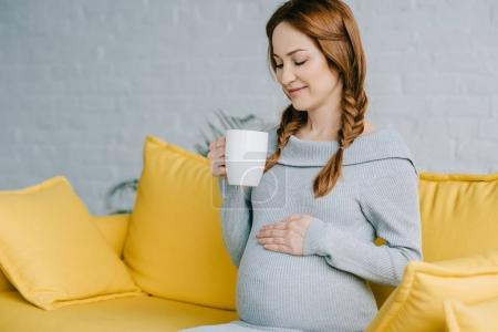 Photo for Cheerful pregnant woman holding cup of tea in living room - Royalty Free Image