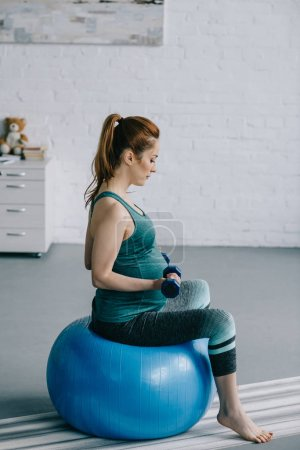 side view of beautiful pregnant woman exercising with dumbbells on fitness ball in living room