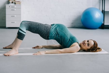 beautiful pregnant woman exercising on yoga mat in living room