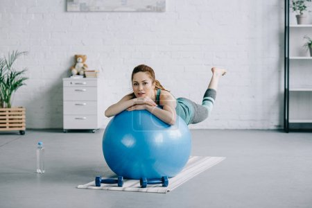 beautiful pregnant woman exercising on fitness ball in living room