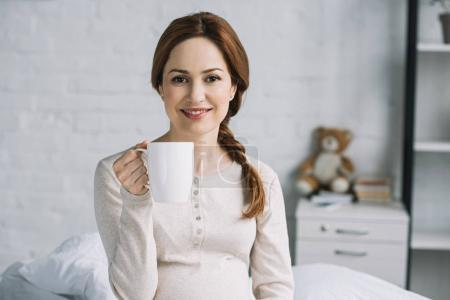 smiling beautiful pregnant woman holding cup of tea and looking at camera in bedroom