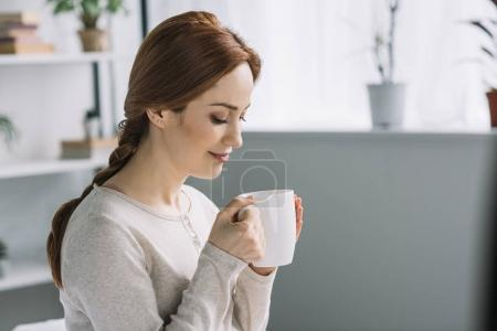 Photo for Side view of beautiful pregnant woman drinking tea at home - Royalty Free Image