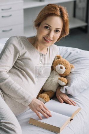 beautiful pregnant woman lying on bed with teddy bear and book