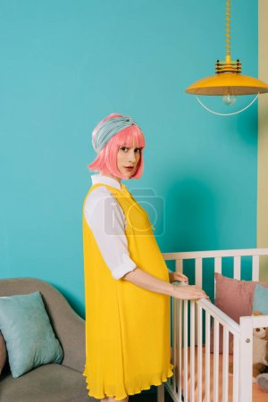 stylish pregnant pin up woman with pink hair standing near baby cot in child room