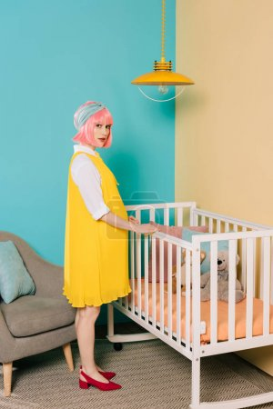 retro styled pregnant pin up woman with pink hair standing near baby bed