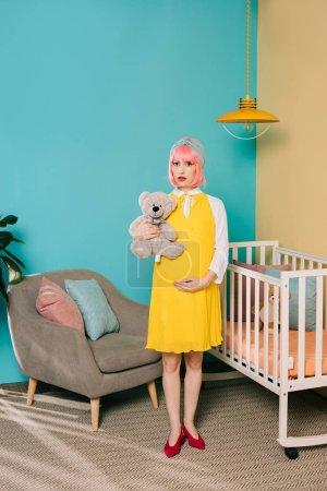Photo pour Rétro style enceinte pin-up femme avec commandes de cheveux roses avec ours en peluche dans la chambre d'enfant - image libre de droit