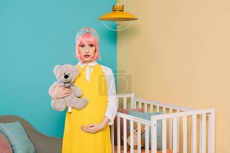 Photo pour Rétro style pin-up enceinte de femme avec les cheveux roses tenue d'ours en peluche dans la chambre d'enfant - image libre de droit