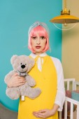 portrait of retro styled pregnant pin up woman with pink hair holding teddy bear in child room