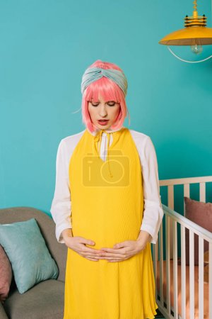 attractive pregnant pin up woman with pink hair touching belly in child room