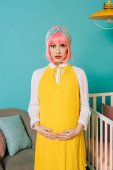 pregnant pin up woman with pink hair touching belly in child room