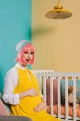 happy pregnant pin up woman with pink hair touching belly and looking at camera