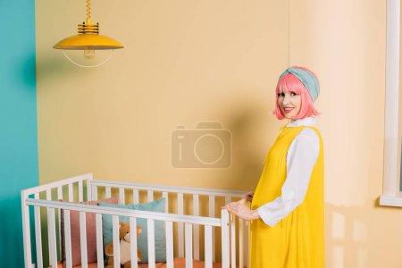 Photo pour Souriant rétro style pin-up enceinte de femme aux cheveux roses se tenant près lit bébé dans la chambre d'enfant - image libre de droit