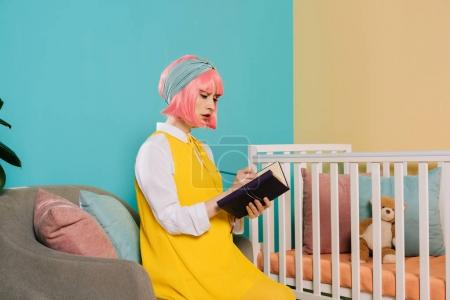 retro styled pregnant pin up woman with pink hair writing something to notebook in child room