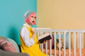 surprised stylish pregnant pin up woman with pink hair holding notebook and pencil near baby cot