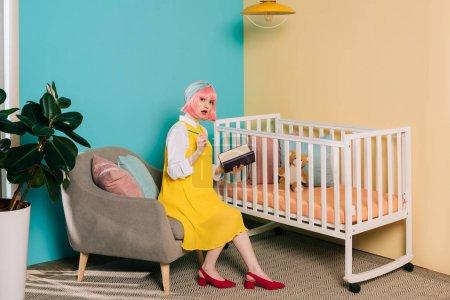 Photo pour Surpris élégante enceinte pin-up femme avec les cheveux Rose tenant portable et en regardant la caméra près de bébé - image libre de droit