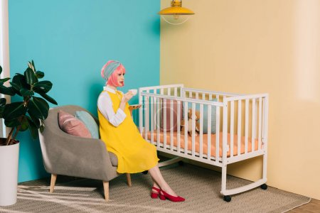 side view of retro styled pregnant pin up woman sitting near baby cot with cup of tea in child room