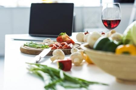 laptop, glass of red wine and vegetables on kitchen table