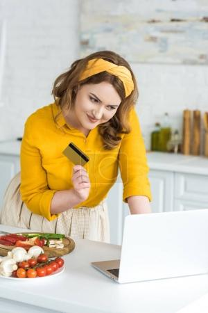 Photo for Smiling beautiful woman holding credit card and looking at laptop at kitchen - Royalty Free Image