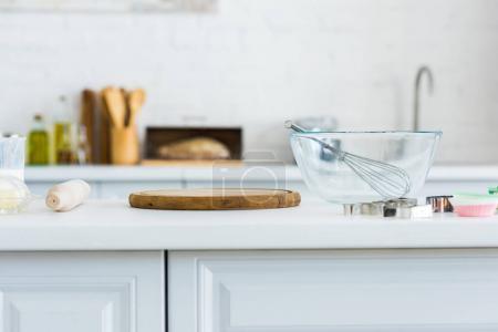 rouleau à pâtisserie, planche à découper et le bol avec le fouet sur le comptoir de cuisine