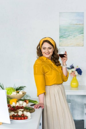 beautiful woman holding glass of wine and looking at vegetables in kitchen
