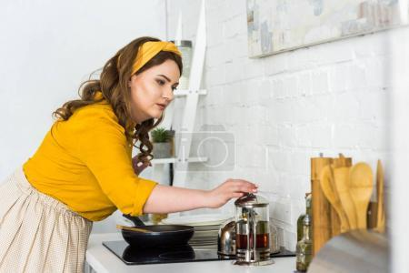 Photo for Side view of beautiful woman cooking in kitchen - Royalty Free Image