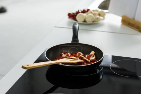 frying pan with delicious vegetables on electric stove in kitchen