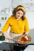"""Постер, картина, фотообои """"красивая женщина, положить овощи на сковороде на кухне"""""""