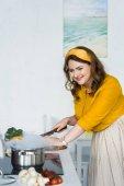 """Постер, картина, фотообои """"красивая женщина резки овощей и глядя на сковороде на электрическая плита на кухне"""""""